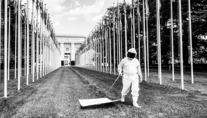 Postava v popředí v bílém ochranném obleku a kukle přejíždí po trávníku bílým plátném uchyceným na tyči. Okolo jsou v řadách stožáry s mnoha vlajkami, v pozadí je honosná budova.